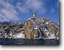Stock photo. Caption: Split Rock Lighthouse   from Lake Superior Split Rock Lighthouse   State Historical Site,  Minnesota -- light lights station stations lighthouses parks great lakes region united states america designated sites direction guidance navigation navigational aid aids midwestern midwest snow covered snowy solid permanent secure winter building buildings imposing