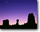Stock photo. Caption: Balanced Rock     and new moon Arches National Park Colorado Plateau,  Utah -- desert summer deserts rock canyons country parks plateaus landscape landscapes tourist travel destination destinations spire spires butte buttes canyon strength moons slickrock skies clear twilight evening dusk silhouette silhouettes landmarks attraction