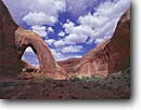 Stock photo. Caption: Broken Bow Arch Willow Gulch Glen Canyon National Recreation Area Colorado Plateau,  Utah -- united states america rock formation formations canyons red rock country sandstone carved backcountry remote spring areas arches navajo puffy clouds sunny walls lesser known