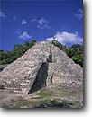 Stock photo. Caption: Mayan ruins from the Classic Period Pyramid of Coba,  Northwest of Tulum Quintana Roo Yucatan,  Mexico -- international travel travels traveling Mexican north america ancient history historical tropical vacation vacations ruin temple winter december national park persistance strength tourist building buildings stone pyramids archeological sunny blue latin
