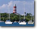 Stock photo. Caption: Elbow Cay Lighthouse  and Hope Town Harbor Hope Town, Elbow Cay Abaco, Bahamas -- stripped strips lighthouses harbors harbour harbours sailboat sailboats winter light station stations safty protection beacon beacons direction guidance pharos navigation america navigational aids abacos travel tourist destination destinations vacation