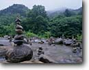 Stock photo. Caption: Stone offerings   Near Shinghungsa Temple Soraksan National Park   near the East Coast Republic of South Korea -- sokcho stacked stones balance balanced creek creeks forest forests asia asian korean peninsula parks world travel tourist destination destinations mountain mountains summer landscape landscapes international religious sites site landmarks landmark