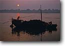 Stock photo. Caption: Boat carrying firewood to cremation ghets Ganges River at Sunrise, Benares Utter Pradesh, India -- international travels travel indian tourist destination destinations asia asian timeless scene holy holiness quiet landscape landscapes people persons immersed spiritual places place ritual rituals boats ancient traditions traditional tradition river