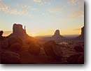 Stock photo. Caption: Sunrise over West & East Mitten Buttes Monument Valley Monument Valley Navajo Tribal Park Colorado Plateau,  Arizona -- indian native american canyon country parks deserts desert butte southwest dramatic summer united states america landscapes travel tourist destination destinations landmark landmarks red rock sunrises sunbursts southwestern attraction attractions