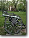 Stock photo. Caption: Civil war cannon and Elkhorn Tavern Pea Ridge National Military Park Benton County Arkansas -- cannons wheel wheels spring civil war wars parks battlefield battlefields united states america travel tourist history attraction attractions spring cloudy rain rainy historic historical landmark landmarks history buildings building exhibit exhibits