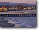 Stock photo. Caption: The Boardwalk and Municipal Pier   from Cowell Beach Santa Cruz Santa Cruz County,  California -- amusement park parks roller coaster coasters beaches piers pacific coast coasts united states america urban tourist attraction attractions winter  enjoyment laughter leisure excitement beaches shore shores shoreline shorelines boardwalks wharf wharfs