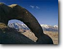 Stock photo. Caption: Eroded granite arch and Lone Pine Peak Alabama Hills, Bishop Resource Area BLM Sierra Nevada Mojave Desert, California -- pines tree trees spring strength tenacity forests mountains united states scenics great basin endurance travel tourist destination destinations alpine power weathered sunny clear icon iconic landmarks landmark famous arches sierras snow  scenic landscapes
