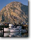Stock photo. Caption: Commercial fishing boats Morro Bay San Luis Obispo County California -- harbors mountains peaks boat vessels vessels harbour harbours quaint village villages united states america summer southeast town towns docks dock wharf wharfs morning clear building buildings sunny spring blue skies refelction reflections anchored anchor