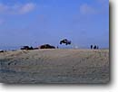 Stock photo. Caption: Jumping truck Oceano Dunes State Vehicular Recreation Area Pismo Beach  San Luis Obispo County,  California -- parks landscape landscapes southern sunny parks popular blue skies clear vehicles outdoor areas trucks people persons highway motor beaches designated dune outdoor offroad tracks