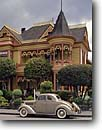 Stock photo. Caption: The Gingerbread Mansion Ferndale Humboldt County California -- americana nostalgic nostalgia united america cloudy historic historical building buildings victorian victorians famous house houses breakfast breakfasts antique classic classics cars automobile automobiles autos home homes mansions landmarks landmark