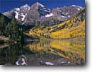 Stock photo. Caption: Maroon Bells reflected in Maroon Lake Elk Mountains White River National Forest Rocky Mountains,   Colorado -- blue spruce aspen fall peak peaks autumn rockies reflections reflection landscape landscapes dramatic majestic mountain color colors forests fourteener fourteeners highcountry arete spectacular breathtaking destination skies sunny perfect scenics scenic