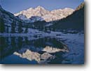 Stock photo. Caption: Maroon Lake and Maroon Bells Elk Mountains White River National Forest Rocky Mountains,  Colorado -- winter snow cold freezing tourist attraction attractions united states america capped peak peaks reflection reflections popular travel destination destinations fourteener fourteeners mountain lakes frigid