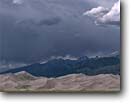 Stock photo. Caption: Great Sand Dunes   and Sangre De Cristo Range Great Sand Dunes National Park Rocky Mountains,  Colorado -- summer landscape national monsoons monsoon season storm stormy parks dune clouds dramatic light summer peaks mountains thunderstorm thunderstorms dark skies breathtaking primal ethereal weather unusual patterns majestic drama dramatic landscapes scenic