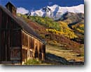 Stock photo. Caption: Old homestead, gambel oaks  and aspens in fall color Iron Mountain from Deep Creek Mesa San Juan Mountains, Colorado -- Rocky barns homesteads wooden vintage antique country trees rural autumn  snow blue skies nostalgia nostalgic cloud clouds structure quaint americana aspen america rural rustic barn durable juans sunny classic abandoned barn building buildings scenics