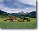 Stock photo. Caption: Tractor and hay baler Teton Valley near Driggs Grand Teton in the Teton Range Teton County,  Idaho -- landscape landscapes west scenics scenic water western rockies blue skies clear agriculture growing growth ranching ranchland ranch industry  progress harvest harvesting tractors john deere balers mountains mountain tetons bales scenic scenics spring