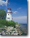 Stock photo. Caption: Cheboygan Crib Lighthouse Cheboygan, Lake Huron Lower Peninsula Cheboygan County,  Michigan -- attraction attractions northern lighthouses stations landscape landscapes scenic scenics protection buildings building great lakes summer light station house houses destinations tower destinations sunny clear blue skies american flags flag flying shore