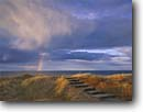 Stock photo. Caption: Rainbow Wooden stairs leading to Lake Superior Park Point, Duluth St. Louis County,  Minnesota -- united states climbing storm stormy dunes evening light great lakes stairway to heaven rainbows trail trails lakeside spiritual ascending city cities near major areas parks landscape landscapes steps belief gold upward rising religious inspire inspiration