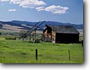 Stock photo. Caption: Beaverslide and hay barn   in the Philipsburg Valley   and the John Long Mountains Granite County,  Montana -- barns homestead homesteads wooden vintage antique rural summer blue skies nostalgia nostalgic quaint americana rocky beaverslides barb wire fence fences west stacking sunny landscape landscapes heritage building buildings rustic truck trucks ranching