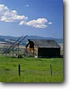 Stock photo. Caption: Beaverslide and hay barn   in the Philipsburg Valley   and the John Long Mountains Granite County,  Montana -- barns homestead homesteads wooden vintage antique rural summer blue skies nostalgia nostalgic quaint americana rocky beaverslides barb wire fence fences west stacking rockies tool tools sunny landscape landscapes heritage building buildings rustic truck
