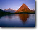Stock photo. Caption: Sunrise on Mt. Gould and Grinnell Point   from Swiftcurrent Lake,  Many Glacier Glacier National Park Rocky Mountains,  Montana -- united states america summer peak peaks parks lakes northern world heritage site sites rockies landscape landscapes tourist travel destination destinations dramatic placid tranquil mountain morning glacial carved  sunrises alpenglow