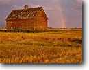 Stock photo. Caption: Rainbow and barn   near Kalispell Rocky Mountains Montana -- united states america summer landscape meadow meadows barns buildings building rainbows hay field hayfield agriculture farm ranch ranchland