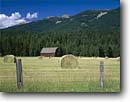Stock photo. Caption: Ranch on Route 200   near Heron Rocky Mountains Montana -- landscape landscapes scenic scenics scene barns building buildings sunny clear blue skies wooden grasses pastoral rural agriculture mountain rockies ranches ranching ranchland farming peaceful bucolic bales rolled harvested harvest fences barb wire barbed