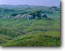 Stock photo. Caption: Looking Glass Rock  in Pisgah National Forest   from the Blue Ridge Parkway near  Tunnel Gap Blue Ridge Mountains,  North Carolina -- forests southeast southeastern woods  spring landscape landscapes tranquil vista vistas peaks mountain view views expansive hardwood hardwoods dome domes national park parks attractions attraction landmark landmarks clear sunny solid rocks trust time