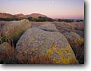 Stock photo. Caption: Mount Scott at sunset Wichita Mountains Wildlife Refuge Comanche County Oklahoma -- tourist destination destinations attraction attractions sunny blue landscape landscapes clear scenic scenics scene tranquil moonrise moonrises moon moons sunsets refuges mountain stark harsh habitat lichen boulders granite