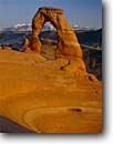 Stock photo. Caption: Delicate Arch   and the La Sal Mountains Arches National Park Colorado Plateau,  Utah -- snow capped icon slick slickrock rock desert parks deserts canyon country landscape landscapes tourist travel destination destinations arid erosion eroded adversity sandstone expansive travel family vacation sunny clear skies blue spring landmarks
