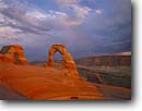 Stock photo. Caption: Sunset clouds over Delicate Arch   and the La Sal Mountains Arches National Park Colorado Plateau, Utah -- united states america evening light storm stormy slick rock desert parks arches deserts canyon country plateaus landscape landscapes tourist travel vacation destination destinations arid dry erosion eroded adversity slickrock sandstone weathering weather