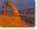 Stock photo. Caption: Sunset clouds, Delicate Arch   and the La Sal Mountains Arches National Park Colorado Plateau, Utah -- united states america evening light storm stormy slick rock desert parks arches deserts canyon country plateaus landscape landscapes tourist travel vacation destination destinations arid erosion eroded adversity slickrock sandstone weathering weather