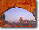 Stock photo. Caption: Turret Arch from North Window   at sunrise Arches National Park Colorado Plateau,  Utah -- united states america evening light storm stormy slick rock desert parks arches deserts canyon country plateaus landscape landscapes tourist travel vacation destination destinations arid erosion eroded adversity slickrock sandstone weathering weather