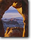 Stock photo. Caption: View through Delicate Arch at sunrise Arches National Park Colorado Plateau, Utah -- united states america evening light slick rock desert parks arches deserts canyon country plateaus landscape landscapes tourist travel destination destinations arid dry erosion eroded adversity sandstone red slickrock arches snow snowy winter wintery