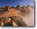 Stock photo. Caption: Delicate Arch  and fog Arches National Park  Colorado Plateau,  Utah -- united states america desert deserts red rock canyons country plateaus spiritual landscape landscapes tourist travel destination destinations arches buttes canyon cold strength ethereal family vacation sandstone slickrock sunny clear blue sky skies