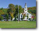 Stock photo. Caption: United Church on the village green Chelsea Orange County Vermont -- east country countryside autumn fall trees destination travel north northeast quaint colors color maple  churches worship religion steeple rural peace peaceful picturesque spiritual family flag pole flagpole white sunny clear blue skies buildings building