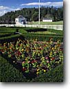Stock photo. Caption: Formal Garden,  Guardhouse   Commissary and Garrison Bay San Juan Island National Historical Park, San Juan Islands,  Washington -- forts historic historical memorials pacific coast safety protection protected northwest northwestern parks gardens flagpole military protected protection guarded fences white pickett picket sunny blue skies clear plot building buildings history safe