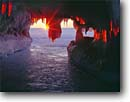 Stock photo. Caption: Sunset and sea caves in winter   at Squaw Bay Apostle Islands National Lakeshore Lake Superior, Wisconsin -- landscape landscapes scenic scenics shore isolated alone trust parks great lakes lakeshores cave environment snow icey icicles cold freezing frozen great lakes park wondow scenic scenics scene northern midwestern midwest sunbeam sunbeams sunbursts