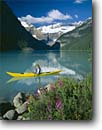 Stock photo. Caption: Kayaker on Lake Louise Banff National Park Rocky Mountains Alberta, Canada -- landscape landscapes scenics scenic lakes parks mountain glaciers glacial silt turquoise color colour classic view views vista vistas summer boats canoes canoe activity outdoor recreation kayak kayaking person woman women people sports yellow boat