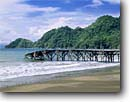 Stock photo. Caption: Old pier Herradura Beach   and Conejo Point Herradura Bay Puntarenas Province,  Costa Rica -- trees beaches caribbean ocean wave waves coastal tropical destination destinations travel tourist warm sunny secluded exotic solitude temperate holiday latin american central america piers docks broken bridge nowhere danger dangerous