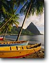 Stock photo. Caption: Local made fishing  boats Soufriere Bay and Petit Piton St. Lucia Windward Islands,  Lesser Antilles -- saint tree palm palms caribbean seas tropical destinations destination vacation vacations landmarks pitons tourist travel exotic warm climate ocean wooden boat leisure relaxation idyllic colorful colourful colours colour classic landmark beach beaches