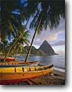 Stock photo. Caption: Local made fishing  boats Soufriere Bay and Petit Piton St. Lucia Windward Islands,  Lesser Antilles -- saint tree palm caribbean palms seas tropical destinations destination vacation vacations landmarks pitons tourist travel exotic warm climate ocean wooden boat leisure relaxation idyllic colorful colourful colours colour landmark sunny beach beaches