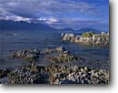 Stock photo. Caption: Seaward Kaikoura Range   from Kaikoura Bay South Pacific Ocean South Island,  New Zealand -- tidepool tidepools mountains rocky shore shoreline shorelines morning summer travel destination destinations tourist ranges seascape seascapes oceans bays harbor harbors harbour harbours peaks peak cloudy clouds rugged