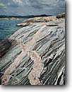 Stock photo. Caption: Migmatite,  Oiseau Bay Pukaskwa National Park Lake Superior Ontario,  Canada -- glacial polished shield canadian lakeshore lakeshores rocky shore shoreline bays lakes parks north america summer great metamorphized metamorphic rock rocks geology geologic landscape landscapes region striped rocks veins clouds cloud