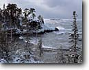 Stock photo. Caption: West of Pancake Point Lake Superior Ontario,  Canada -- canadian lakeshore lakeshores shore shoreline lakes parks north america great frozen freezing snow covered winter wintery cold island islands landscape landscapes cliffs tree trees forest forests winterscape overcast stormy storm clouds cloud waves