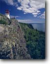 Stock photo. Caption: Slate Islands Lighthouse Lake Superior Slate Islands Provincial Park Ontario,  Canada -- light station cliff summer great lakes lighthouses island canadian parks protection beacon beacons direction guidance navigation america navigational aid aids landscape landscapes rock solid cliffs great lakes region scenic scene sunny clear sky blue