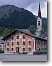 Stock photo. Caption: Church in Holzgau Lech River Valley Vorarlberg Alps,  Austria -- churches travel destination destinations tourist mountains europe european place worship christian christianity austrian women woman people sitting bench faith community steeple steeples wisdom outside buildings building scenic scenics landscapes scenics