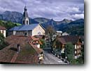 Stock photo. Caption: Church in Manigod Chaine de Aravis Rhone-Alps Region French Alps,  France -- mountains fall autumn church churches colors rural pastoral europe european clock clocks mountain village villages rustic landscape landscapes quaint cloudy road buildings building roads streets street steeple steeples religous faith places worship scenic