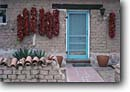 Stock photo. Caption: Red chilis hanging outside a house Tucson Arizona -- building buildings architecture chilli wreaths door window doors windows detail details houses southwestern southwest decor chili chillies pepper cityscape cityscapes