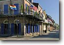Stock photo. Caption: Royal Street French Quarter (Post Katrina) New Orleans, Louisiana -- city cities sunny clear historic historical scenic destination destinations landmark landmarks attractions flags flag spring balconies balcony streets storefronts wrought iron scenics shuttters shuttered window windows buildings building american