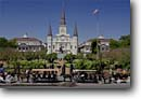 Stock photo. Caption: St. Louis Cathedral   from Jackson Square French Quarter (Post Katrina) New Orleans, Louisiana -- city cities sunny clear historic historical scenic destination destinations landmark landmarks attractions attraction horses flags spring streets scenics parks plaza plazas buildings building horse drawn carriage horses carriages churches people flag